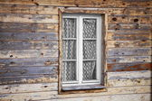 Rural much neglected window in wooden wall — Stock Photo