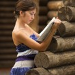 Girl with the book at the wall of wooden house — Stock Photo