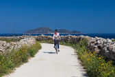 Adult woman is biking at Favignana Island — Foto Stock