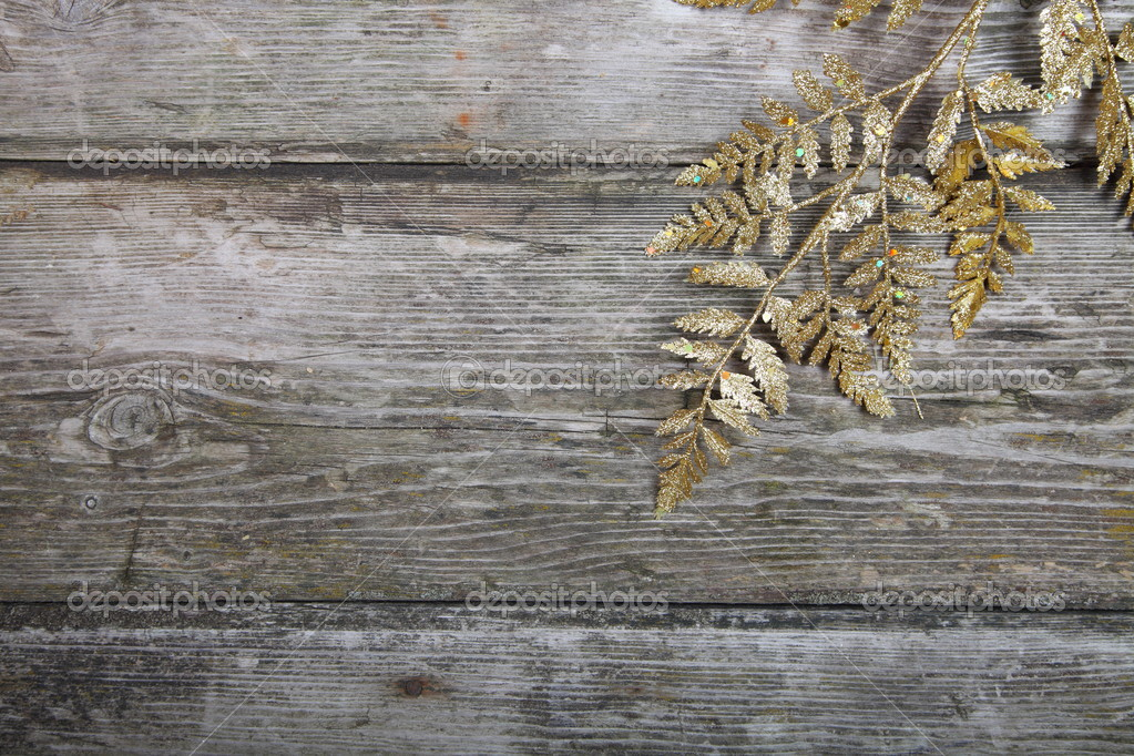 Christmas decorations: golden twig on a wooden background  Stock Photo #13639276
