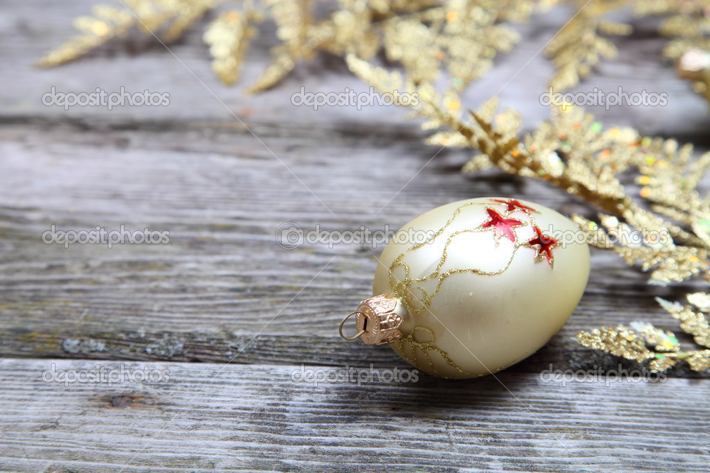 Christmas decorations: golden twig and balls on a wooden background — Stock Photo #13639282