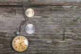 Old clock and coins — Stock Photo