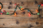 Christmas lights on a wooden background — Stock Photo