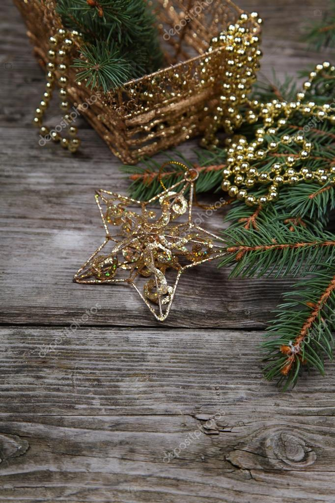 Golden Christmas decorations and spruce branches on a wooden table  Stock Photo #14101437