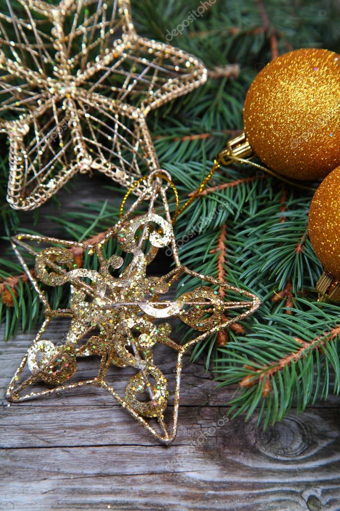 Golden Christmas decorations and spruce branches on a wooden table — Stock Photo #14101442