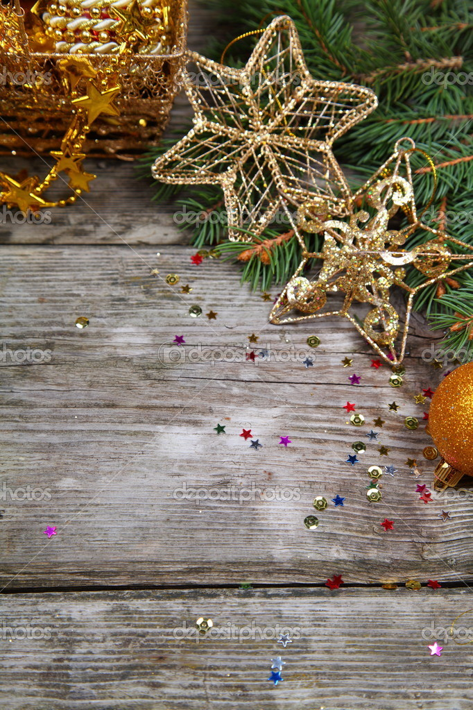 Golden Christmas decorations and spruce branches on a wooden table — Stock Photo #14101449