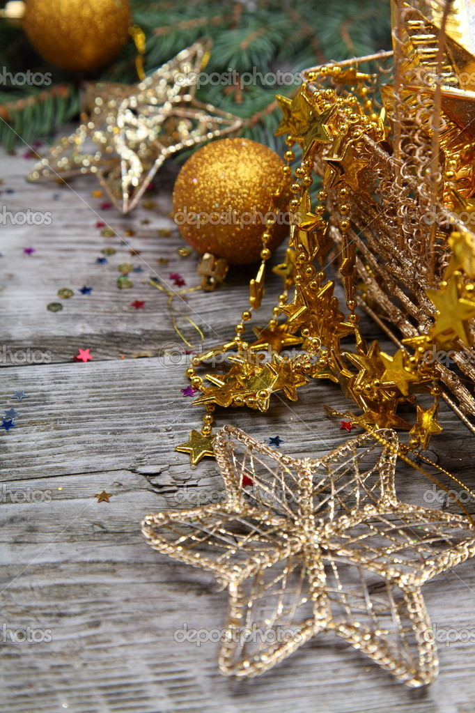 Golden Christmas decorations and spruce branches on a wooden table  Stock Photo #14101450