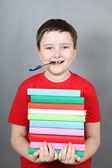 Jongen met een pen in zijn mond houden een stapel boeken — Stockfoto