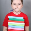 Boy with a pen in his mouth holding a stack of books — Stock Photo #47107117