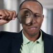 Black Man Looking through a magnifying glass — Stock Photo