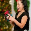 Hispanic Woman Holding a Christmas Present — Stock Photo #13507885