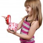 Beautiful little girl opening a present — Stock Photo