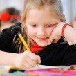 Portrait of happy young girls writing notes with friends in back — Stockfoto