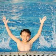 Kid splashing on summer pool — Stock Photo