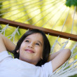 Cute kid lying in hammock at beautiful summer day — Stock Photo