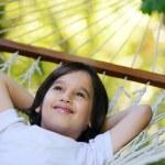 Cute kid lying in hammock at beautiful summer day — Stock Photo