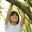 Child in nature holding tree arm - Stock Photo