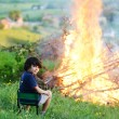 Stock Photo: Kid beside big fire