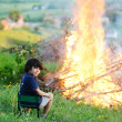 Kid beside the big fire - Stock Photo