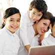Mother with children using laptop at home — Stock Photo