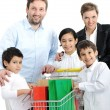 Happy family with a shopping cart — Stock Photo