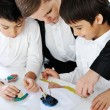 Stock Photo: Mother working with sons on homework project