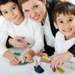Mother working with sons on homework project — Stock Photo #13335367