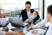 Business taking care of baby in office — Stock Photo