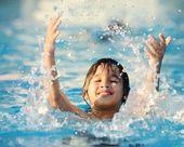 Chico chapoteando en la piscina de verano — Foto de Stock