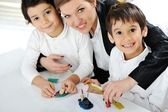 Mother working with sons on homework project — Stok fotoğraf
