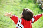 Niño extendida contra el cielo — Foto de Stock