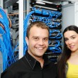 Two administrators, male and female, at server room — Stock Photo