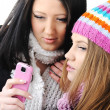 Two female friends reading sms message on cell phone — 图库照片
