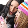 two female friends reading sms message on cell phone — Stock Photo