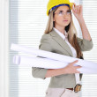 Female engineer with helmet and blueprints at business office — Stock Photo