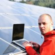Male engineer using laptop, solar panels in background — Stock Photo #21354493
