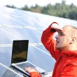 Foto Stock: Male engineer at work place, solar panels in background