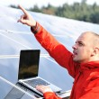 Male engineer using laptop, solar panels in background — Stock Photo #21354569