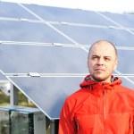 joven trabajador masculino con paneles solares en fondo — Foto de Stock