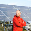 Stock fotografie: Young male worker with solar panels in background