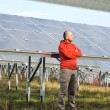 Foto Stock: Young male worker with solar panels in background