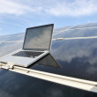 Laptop on  photovoltaic solar panels against blue sky - Stock Photo