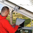 Stock Photo: Engineer working with laptop by solar panels