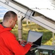 Engineer working with laptop by solar panels — Stock Photo #21356171