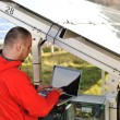Engineer working with laptop by solar panels — Stock Photo
