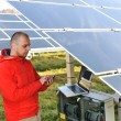 Stock Photo: Engineer working with laptop by solar panels, talking on cell phone