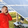 Engineer working with laptop by solar panels, talking on cell phone — ストック写真