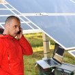 Photo: Engineer working with laptop by solar panels, talking on cell phone