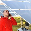 Engineer working with laptop by solar panels, talking on cell phone — Stok fotoğraf