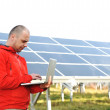 Male engineer using laptop, solar panels in background — Foto Stock